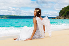 Beautiful young bride with angel wings on the sea coast. Tropica Royalty Free Stock Image