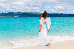 Beautiful young bride with angel wings on the sea coast. Tropical sea in the background. Beautiful young bride with angel wings on the sea coast. Tropical sea stock images