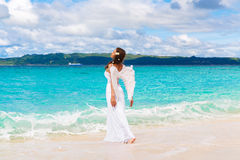 Beautiful young bride with angel wings on the sea coast. Tropical sea in the background. Beautiful young bride with angel wings on the sea coast. Tropical sea stock photos