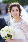 Beautiful young bride with bouquet from white roses Stock Photo