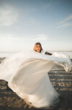 Beautiful young bride with bridal bouquet posing on the background sea.  Royalty Free Stock Image
