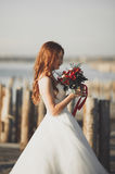 Beautiful young bride with bridal bouquet posing on the background sea Stock Photo