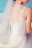 Beautiful young bride with dark curly hair in luxurious wedding dress posing at room Royalty Free Stock Photography