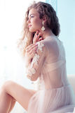Beautiful young bride with dark curly hair in luxurious wedding dress posing at room. Fashion studio photo of beautiful young bride with dark curly hair in stock images