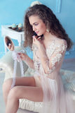 Beautiful young bride with dark curly hair in luxurious wedding dress posing at room Stock Photos
