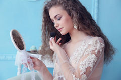 Beautiful young bride with dark curly hair in luxurious wedding dress posing at room Royalty Free Stock Photos