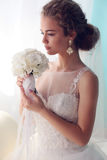 Beautiful young bride with dark curly hair in luxurious wedding dress posing at room Stock Photo