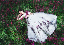 Beautiful young bride in field, happy woman enjoying flowers.beautiful girl lying in the grass and flowers Royalty Free Stock Photos