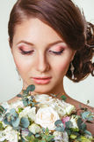 Beautiful young bride with a floral ornament in her hair.Beautiful Woman Touching her Face. beautiful bride with bouquet Royalty Free Stock Photography