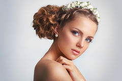 Beautiful young bride with a floral ornament in her hair.Beautiful Woman Touching her Face. Youth and Skin Care Concept on white b Stock Photo