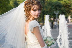 Beautiful young bride with fountain on background Stock Photo
