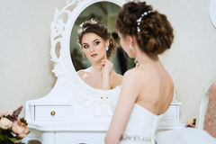 Beautiful young bride in front of the mirror Royalty Free Stock Photos