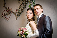 Beautiful young bride and groom in indoor setting Stock Image