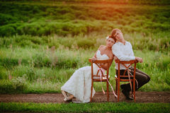 Beautiful young bride and groom kissing sitting chairs in the sunset light Royalty Free Stock Photography