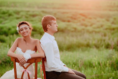 Beautiful young bride and groom kissing sitting chairs in the sunset light Stock Photo
