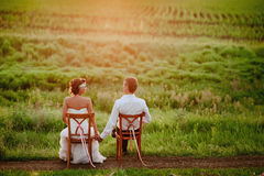 Beautiful young bride and groom kissing sitting chairs in the sunset light Stock Image