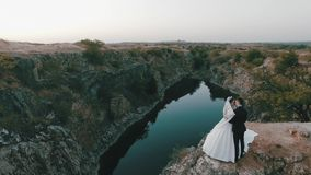 Beautiful young bride and groom stand on a cliff in the background of the river and gently embrace each other. Sunny stock footage