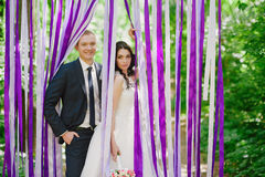 Beautiful young bride and groom at a wedding ceremony when in the background of multi-colored ribbons, marriage, relationships, c Stock Photo