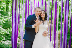 Beautiful young bride and groom at a wedding ceremony when in the background of multi-colored ribbons, marriage, relationships, c Stock Image
