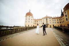 Beautiful young bride and handsome groom dancing outdoors near old mansion at sunset Royalty Free Stock Photo