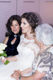 Beautiful young bride  with her mother and grandmother. Portrait of gorgeous  bride smiling  and posing for photo with her family Stock Photo