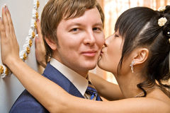 Beautiful young bride kissing groom Royalty Free Stock Image