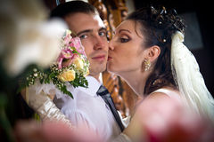 Beautiful young bride kissing groom Stock Images