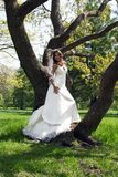 Beautiful young bride leaned against a tree Royalty Free Stock Photos
