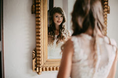 Beautiful young bride looking in the mirror Royalty Free Stock Images