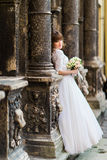 Beautiful young bride looking towards between the columns of old building and holding bridal bouquet Royalty Free Stock Photo