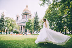 Beautiful young bride in a magnificent wedding dress spinning in nature Stock Photography