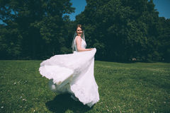 Beautiful young bride in a magnificent wedding dress spinning in nature Royalty Free Stock Photography