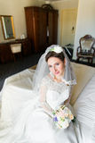Beautiful young bride with makeup, fancy hairstyle in white dress and veil sitting on bed royalty free stock photo