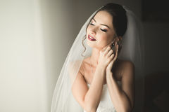 Beautiful young bride with makeup and hairstyle in bedroom, newlywed woman final preparation for wedding. Happy girl Royalty Free Stock Photo