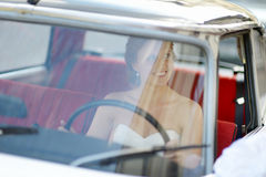 Beautiful young bride portrait in a wedding car Stock Images