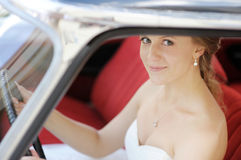 Beautiful young bride portrait in a wedding car Stock Photos