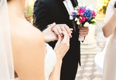 Beautiful young bride putting wedding ring on grooms finger Stock Photos