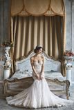 Beautiful young bride, brunette model girl in the stylish and fashionable wedding dress with naked shoulders sits royalty free stock images
