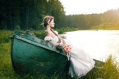 Beautiful young bride sitting on boat Stock Images
