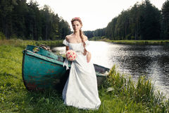 Beautiful young bride sitting on boat Stock Photo