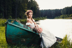 Beautiful young bride sitting on boat Stock Image