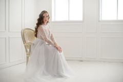 Beautiful young bride sitting on a chair Stock Images