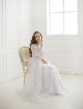 Beautiful young bride sitting on a chair Royalty Free Stock Photography
