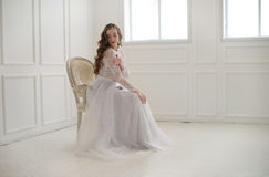 Beautiful young bride sitting on a chair in white room. Royalty Free Stock Image