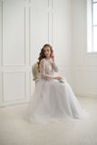 Beautiful young bride sitting on a chair in white room with hand Royalty Free Stock Photography