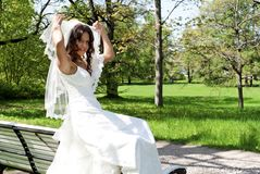 Beautiful young bride sitting on a park bench Royalty Free Stock Photography