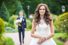 Beautiful young bride standing on lane in summer park Stock Image