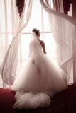 Beautiful young bride standing beside a wind Royalty Free Stock Images
