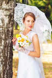 Beautiful young bride standing in the woods Stock Image