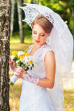 Beautiful young bride standing in the woods with umbrella Royalty Free Stock Image